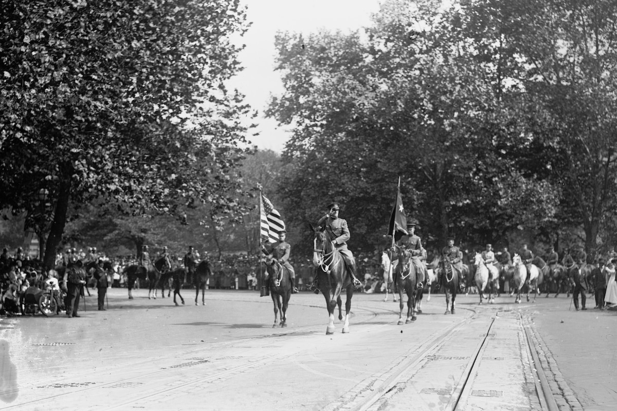 Troops on horseback parade down a street.