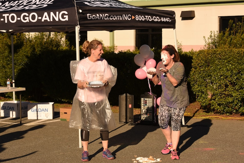 U.S. Air Force Col. Bryony A. Terrell (left), 145th Airlift Wing commander, pies Lt. Col. Lisa Kirk, 145th Mission Support Group commander, in the face for a fundraising event following a 'Living' My Best Life' Color Race, held at the North Carolina Air National Guard (NCANG) Base, Charlotte Douglas International Airport, Nov. 3, 2018. The Color Run, put together by the NCANG Recruiting Office, honors recently deceased U.S. Air Force Recruiter Master Sgt. Valanda Pettis, following her battle with cancer. Master Sgt. Pettis was believed by many to have a colorful personality and would often be heard singing, 'Livin' My Best Life,' during the good and bad days; a true testament to her strength.