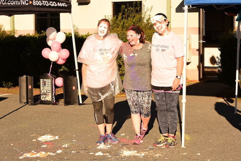U.S. Air Force Col. Bryony A. Terrell, 145th Airlift Wing commander (left), Lt. Col. Lisa Kirk, 145th Mission Support Group commander (center), and Lt. Col. Karen Shook, 145th Maintenance Group commander (right), pose together after being pied in the face for a fundraising event following a 'Living' My Best Life' Color Race, held at the North Carolina Air National Guard (NCANG) Base, Charlotte Douglas International Airport, Nov. 3, 2018. The Color Run, put together by the NCANG Recruiting Office, honors recently deceased U.S. Air Force Recruiter Master Sgt. Valanda Pettis, following her battle with cancer. Master Sgt. Pettis was believed by many to have a colorful personality and would often be heard singing, 'Livin' My Best Life,' during the good and bad days; a true testament to her strength.