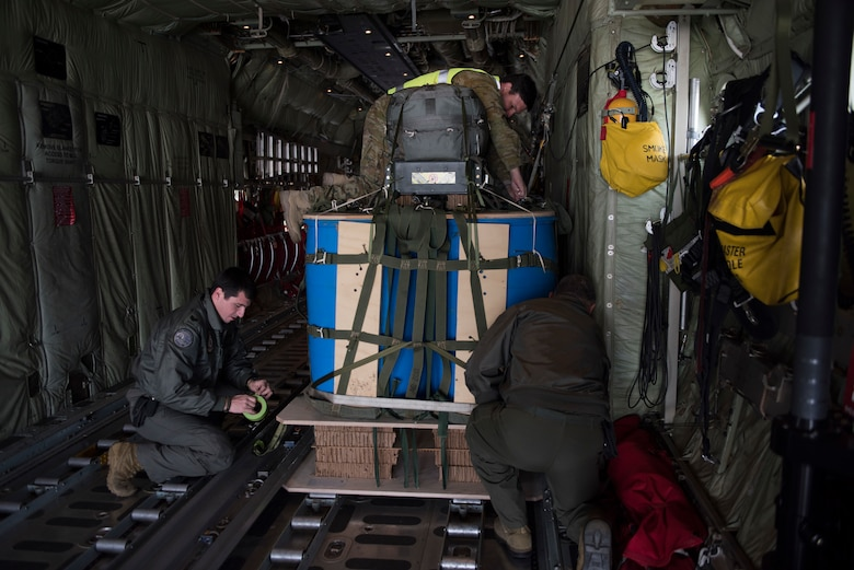 Image of members of the Australian military work together to trap down cargo on a C-130J Super Hercules before a flight Nov. 1, 2018, at Mountain Home Air Force Base, Idaho. One reason the RAAF chose to come to Mountain Home AFB to train is for the terrain, which is very different from Australia.(U.S. Air Force photo by Senior Airman Alaysia Berry)