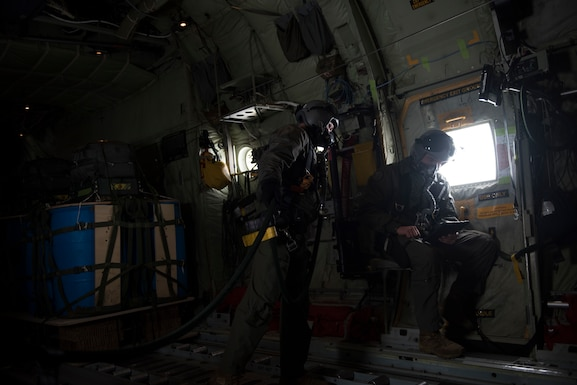 Image of C-130J Super Hercules loadmasters SGT Penny and SGT Lambeth prepare to drop GPS-guided cargo from a C-130J at Saylor Creek Range, Idaho, Nov. 1, 2018. The cargo uses a joint-precision aero-delivery system that guides it to a programmed destination. (U.S. Air Force photo by Senior Airman Alaysia Berry)