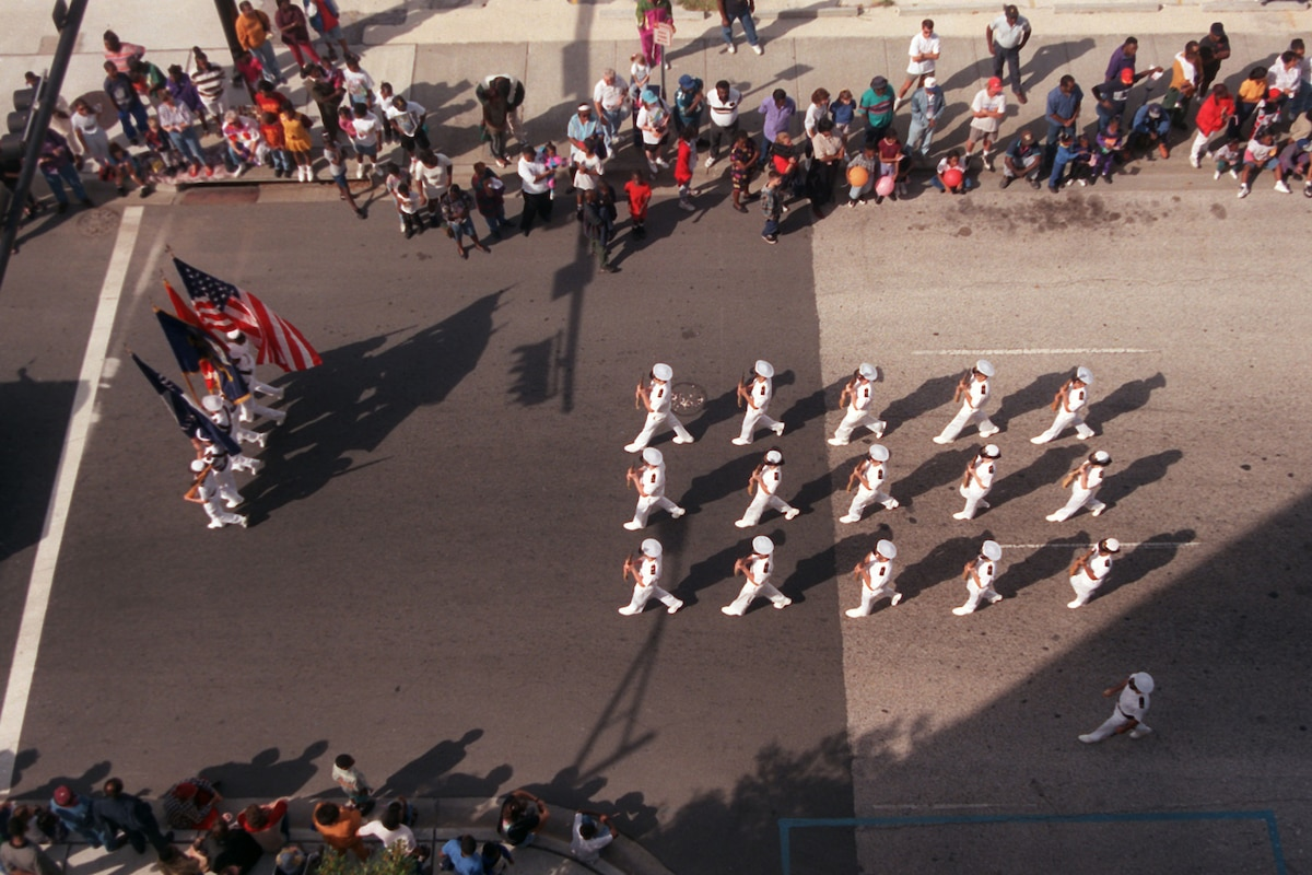 A formation of troops, shown from overhead, march in a parade.