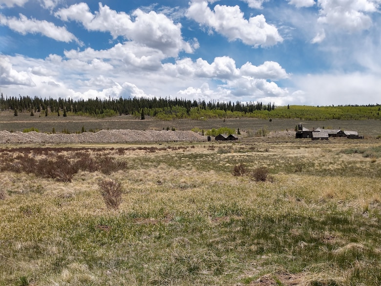 A spring-fed wetland complex associated with Corske Creek (foreground) with historic placer mine tailings, and the remains of the historic Hallenbeck Ranch. (background).