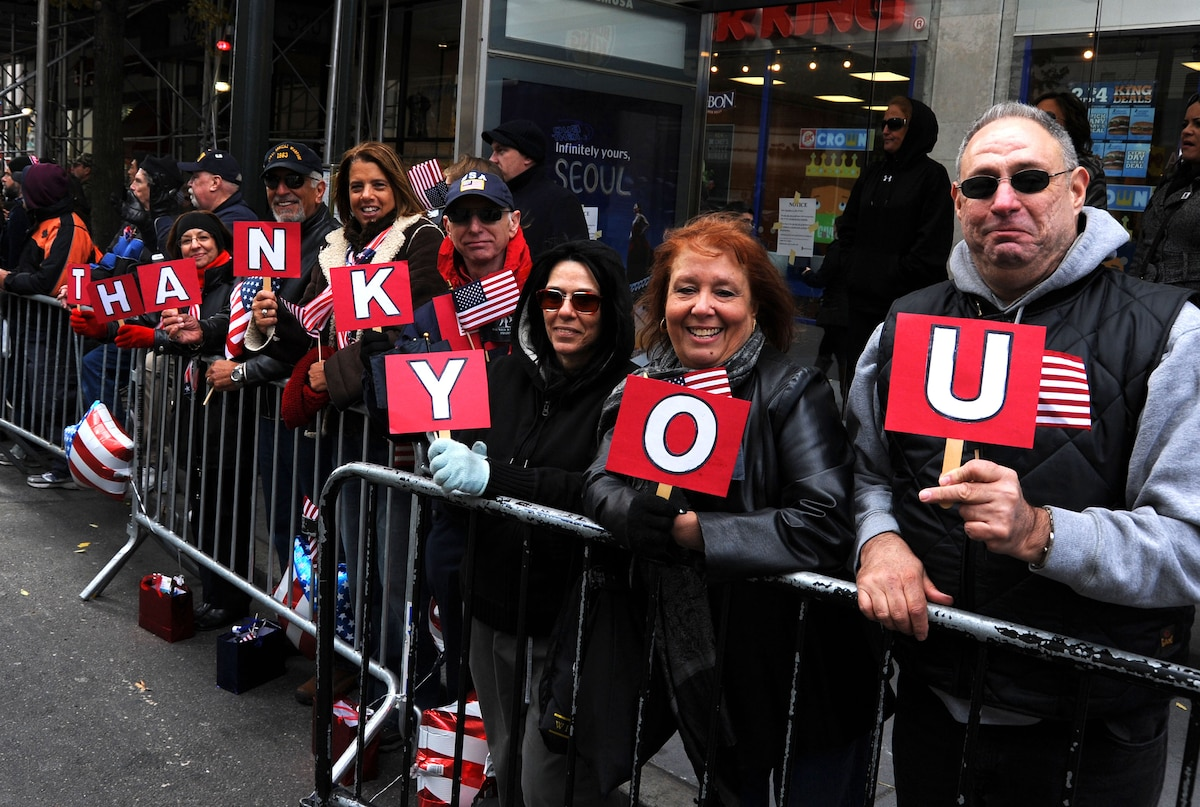 "Smiling spectators hold up letter signs spelling out ""THANK YOU"" along a parade route."