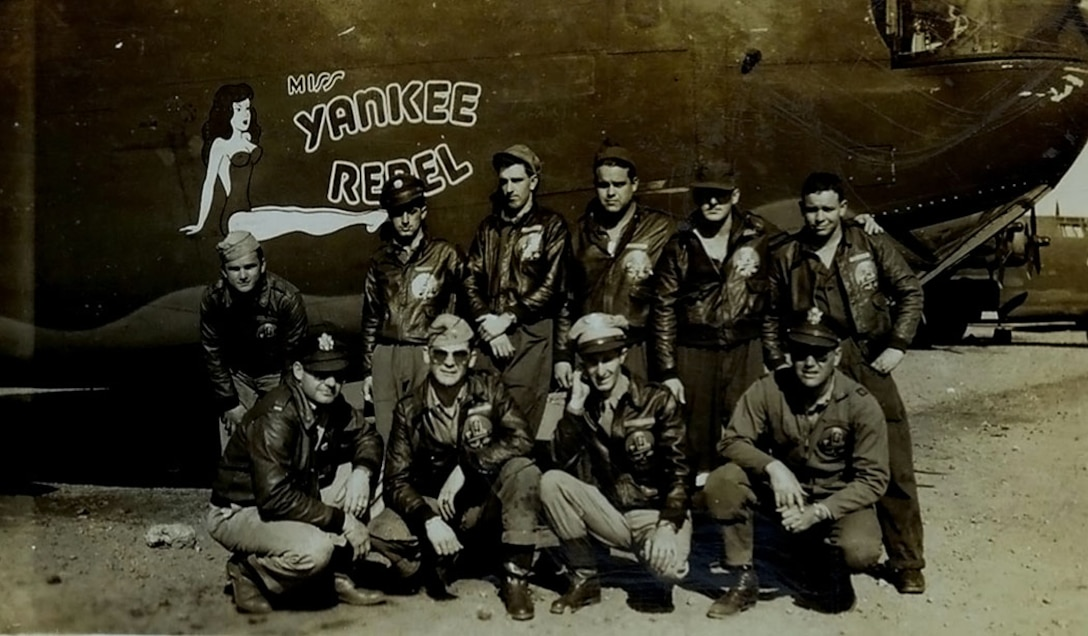 """U.S. Army Air Corps 1st Lt. John D. Crouchley, kneeling, second right, and his crew pose for a photo by their B-24 Liberator, """"Miss Yankee Rebel"""" in 1944. Crouchley was assigned to the 828th Bombardment Squadron, 485th Bombardment Group, Foggia, Italy, and went into combat in May 1944. Just one month later, he paid the ultimate sacrifice for his country when his aircraft was shot down over Bulgaria when he and his crew were returning from a bombing mission over Romania June 28, 1944. (Courtesy photo)"""