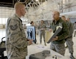 Tech. Sgt. Joshua Rea, with the 552nd Maintenance Squadron's Fabrication Flight, speaks to Gen. Mike Holmes, commander Air Combat Command, about the operations within their shop and the products they are able to reproduce with their 3-D printers, such as the pilot's seat shroud the General is holding.