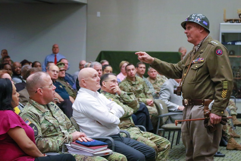 General George S. Patton, Jr., portrayed by Mr. Denny Hair, answers questions about the life and events surrounding the real Gen. Patton at U.S. Army Central's Centennial Celebration held at Patton Hall, November 7. Mr. Hair is among several living historians who came to the event to tell the Third Army story during World War II.