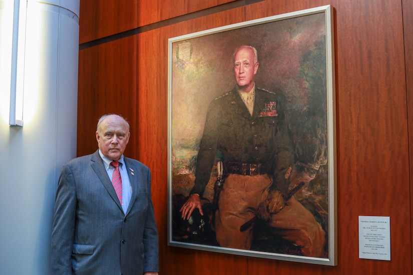 Mr. George Patton Waters, grandson to General George S. Patton, Jr., stands beside the portrait he donated to U.S. Army Central. Mr. Waters attended the USARCENT Centennial Celebration held at Patton Hall, November 7, as a special guest of the command.