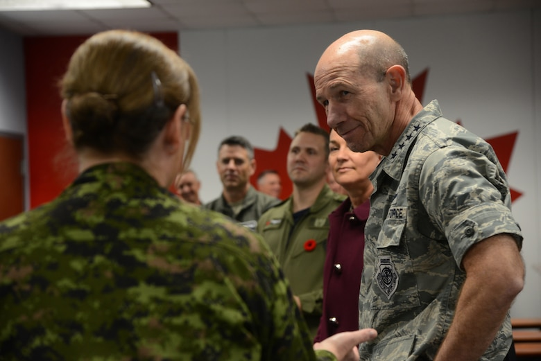 Gen. Mike Holmes, commander Air Combat Command, listens to Master Warrant Officer Lisa Powers, with the 552nd Air Control Wing Canadian Detachment, as she emphasizes the importance of the strategic relationship between the U.S. and Canada and also provides him with an overview of their flying unit operaitons and working environment during his Nov. 1 visit to Tinker.