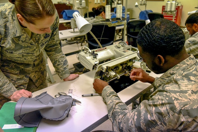 361st Training Squadron aircrew flight equipment apprentice course instructor Master Sgt. Laura Plue, left, watches as Airman Malcom Younge of Atlanta services a sewing machine during training at Sheppard Air Force Base, Texas, Nov. 8, 2018. Airmen spend eight days learning how to sew and maintain the machines to be able to repair fabric and rubber components including protective clothing, thermal radiation barriers, flotation equipment and parachutes. (U.S. Air Force photo by John Ingle)