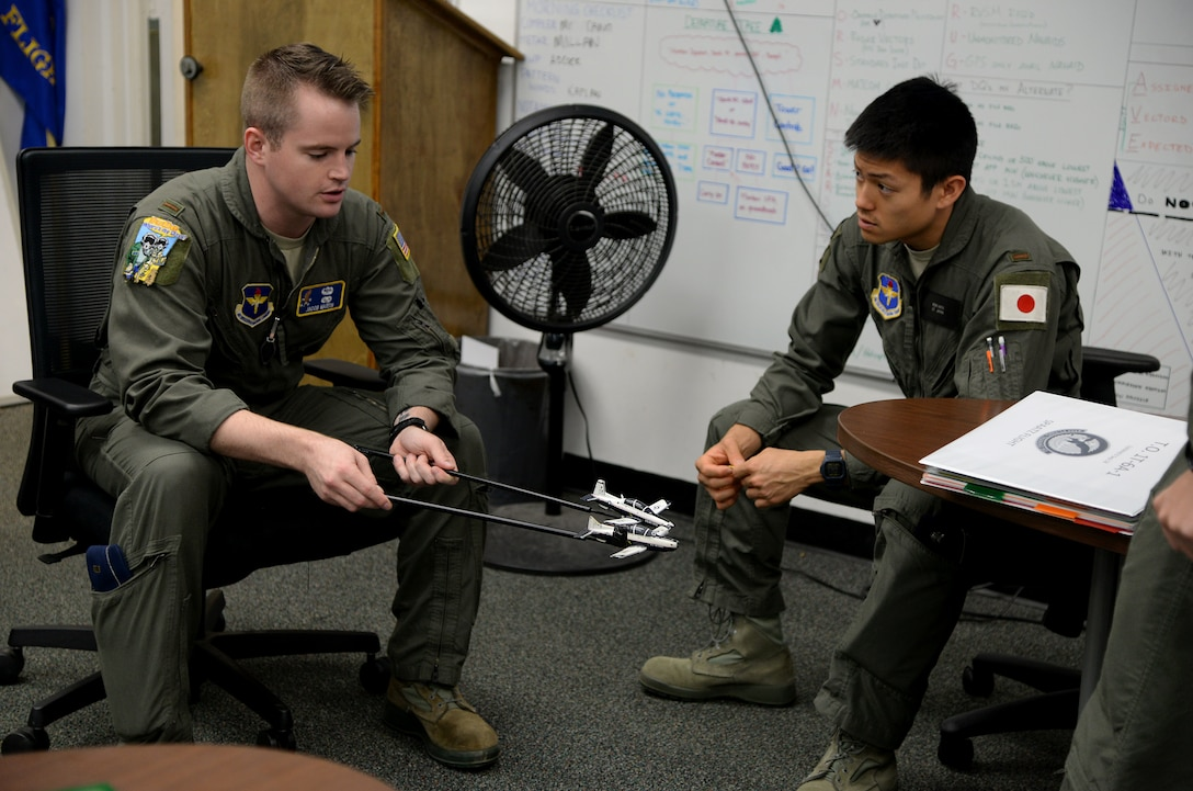 Second Lt. Jacob Martin, 14th Student Squadron student pilot, demonstrates an aerial maneuver to Koki Hata, 14th STUS student pilot, with prop T-6 Texan II's Nov. 5, 2018, on Columbus Air Force Base, Mississippi. Students work together throughout pilot training to learn new or different ways to approach aviation. (U.S. Air Force photo by Airman 1st Class Keith Holcomb)