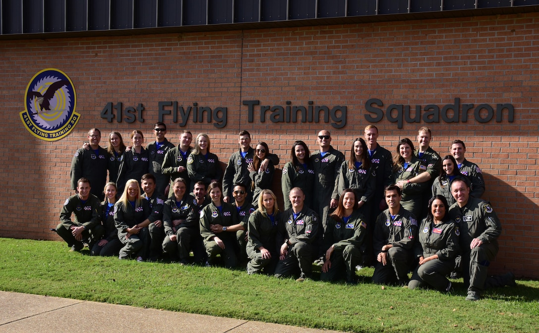 Instructor pilots 41st Flying Training Squadron stand with their spouses Nov. 2, 2018, on Columbus Air Force Base, Mississippi. Spouse flights are annual for the 14th Operations Group to thank spouses as well as show them firsthand what their uniformed family members do every day at work to complete their mission. (U.S. Air Force photo by Elizabeth Owens)