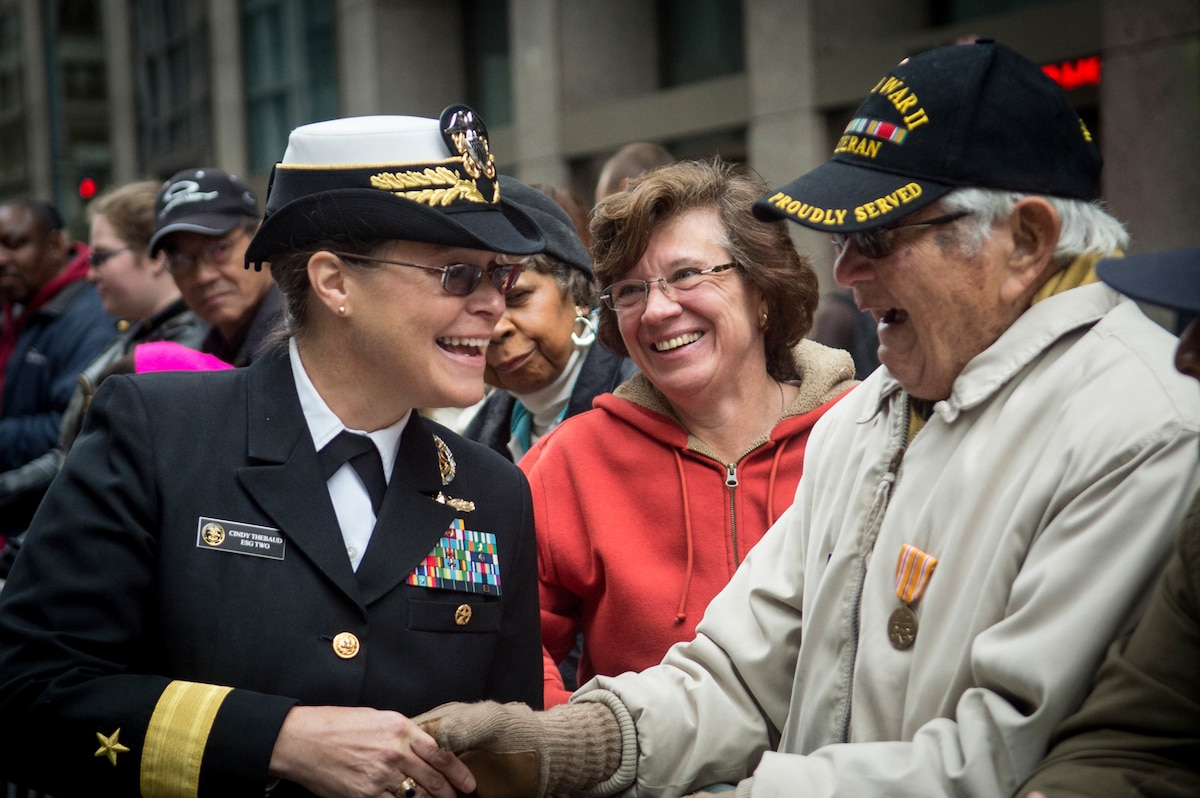 A sailor shakes hands with a veteran at a parade.