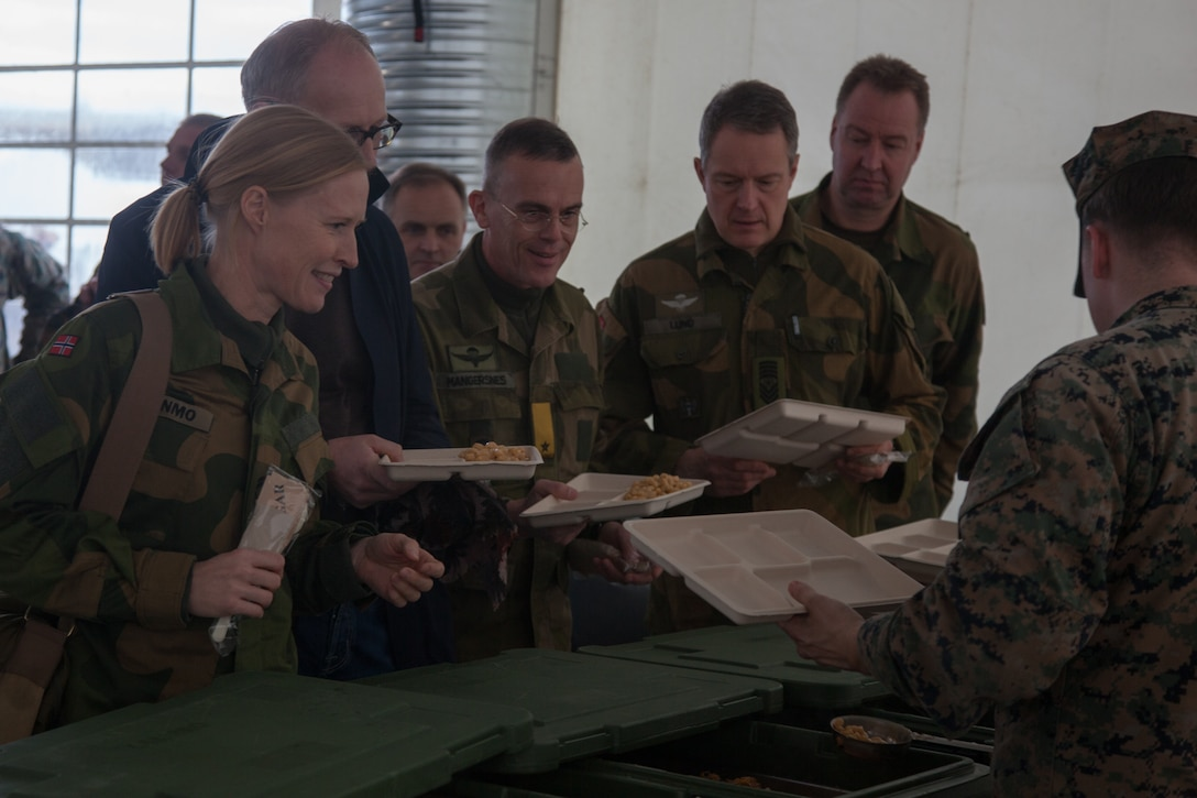 U.S.  Marines with 2nd Marine Logistics Group-Forward (2nd MLG-Fwd) serve lunch to Norwegian military members, in Stjødal, Norway,Nov. 5, 2018. Leaders of the Norwegian military met with leaders and noncommissioned officers (NCOs) of 2nd MLG-Fwd to discuss the role of the Marine Corps NCO during Exercise Trident Juncture 18. The exercise enhances the U.S. and NATO Allies' and partners' abilities to work together collectively to conduct military operations under challenging conditions. (U.S. Marine Corps photo by Lance Cpl. Scott R. Jenkins)