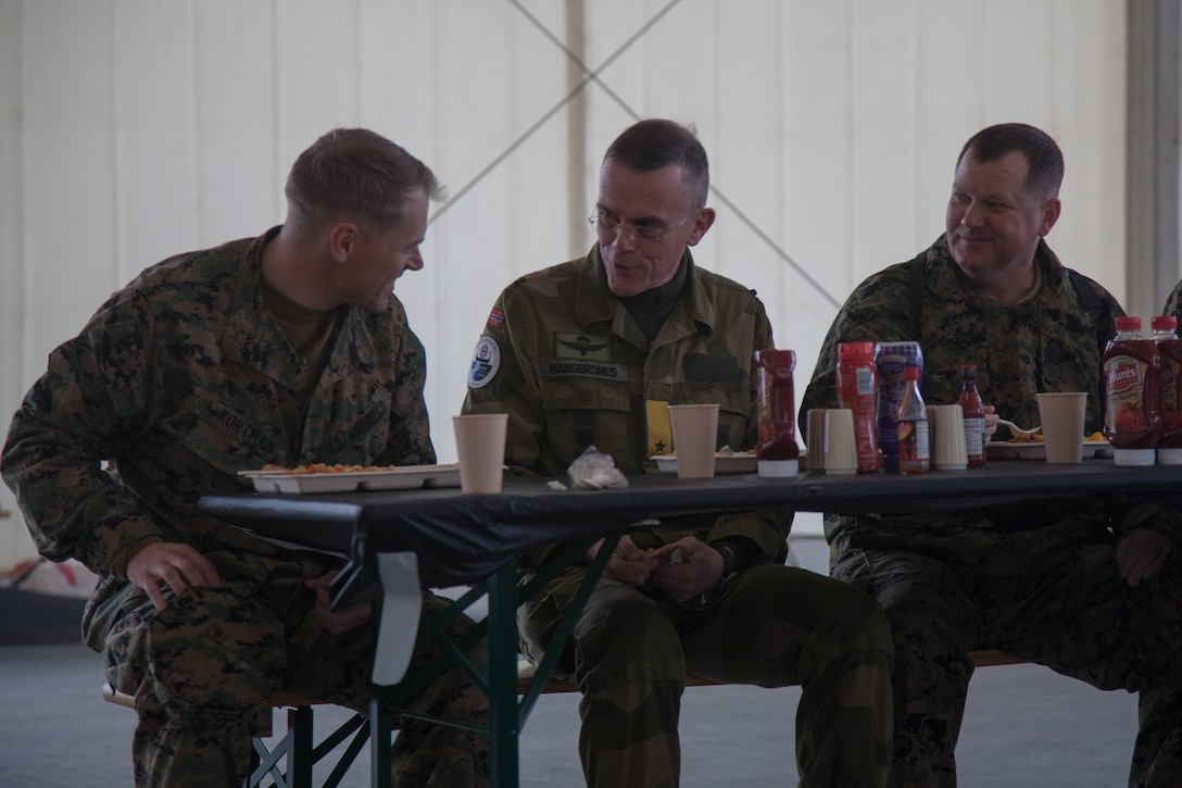 Norwegian Army Brig. Gen. Jon Morten Mangersnes, right, the commander of the Norwegian Land Warfare Center, speaks with  Maj. Duane Kortman Jr., left, and Master Gunnery Sgt. William Jansen, both with 2nd Marine Logistics Group-Forward (2nd MLG-Fwd), in Stjødal, Norway,Nov. 5, 2018. Leaders of the Norwegian military met with leaders and noncommissioned officers (NCOs) of 2nd MLG-Fwd to discuss the role of the Marine Corps NCO during Exercise Trident Juncture 18. The exercise enhances the U.S. and NATO Allies' and partners' abilities to work together collectively to conduct military operations under challenging conditions. (U.S. Marine Corps photo by Lance Cpl. Scott R. Jenkins)