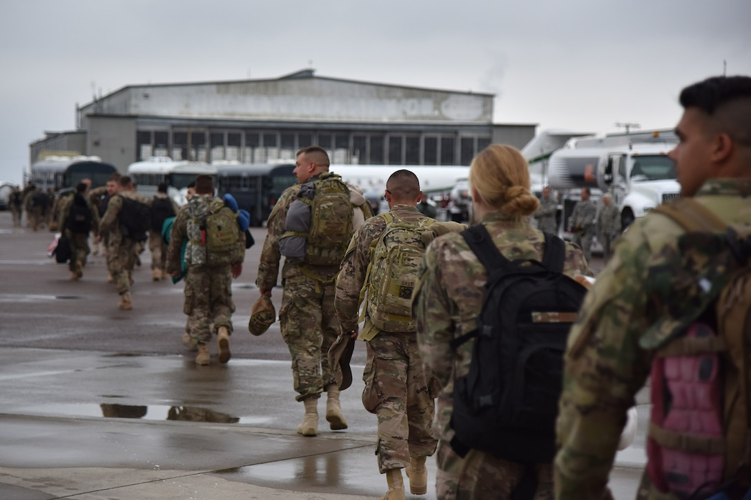 Airmen from the 819th Rapid Engineer Deployable Heavy Operational Repair Squadron Engineers (RED HORSE) walk across the flight line Nov. 5, 2018, at Great Falls International Airport, Mont. Seventy RED HORSE Airmen served for U.S. Africa Command and 100 Airmen served for U.S. Air Forces Central Command. (U.S. Air Force photo by Airman 1st Class Jacob M. Thompson)