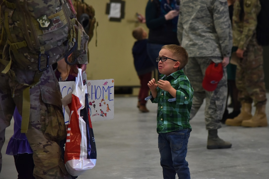 A child watches as his father approaches after returning home from deployment Nov. 5, 2018, at the airfields located on Malmstrom Air Force Base, Mont. RED HORSE Airmen returned home to friends and family after being deployed for approximately seven months. (U.S. Air Force photo by Airman 1st Class Jacob M. Thompson)