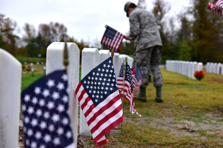 Individuals in uniform lay flags at graves of service members.