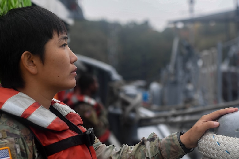 U.S. Army Spc. Mi Rea Lee, 73rd Transportation Company, 10th Trans. Battalion, 7th Trans. Brigade (Expeditionary) seaman, looks over the side of a 900-series Small Tug at Joint Base Langley-Eustis, Virginia, Nov. 5, 2018. The crew for a Small Tug consists of a vessel master, chief engineer, five watercraft operators and four watercraft engineers. (U.S. Air Force photo by Senior Airman Derek Seifert)