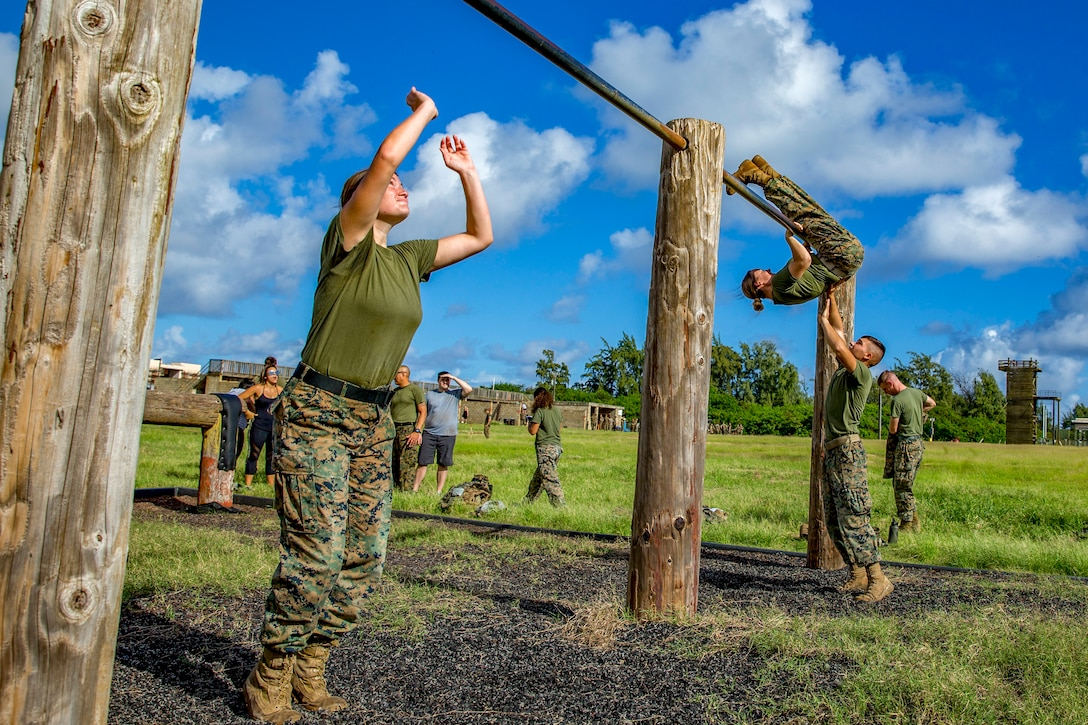 Marine spouses grab an overhead bar obstacle on an outside obstacle course.