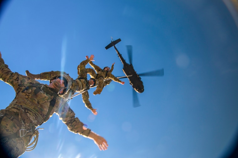 Soldiers hang on a rope attached to a helicopter.