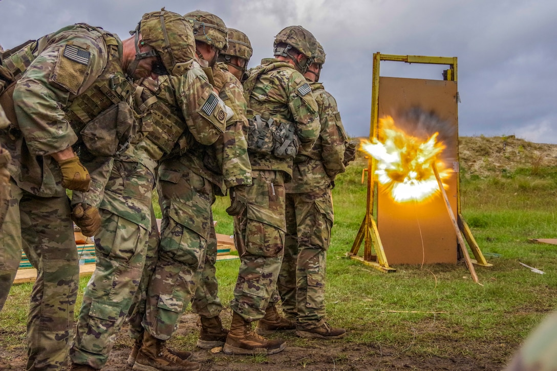 Paratroopers stand together in line as they detonate a charge in a mock door.