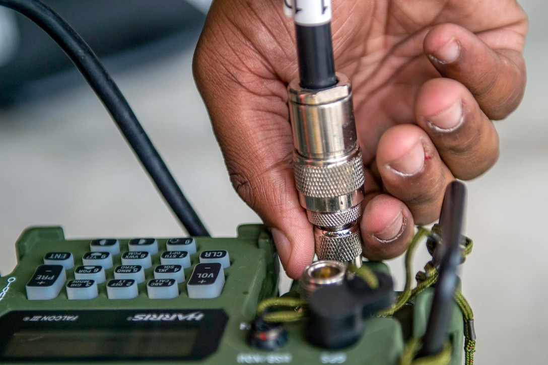 An airman plugs a cord into a communications device.