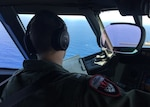 Lt. j.g. Steven Mcintyre, assigned to Ptrol Squadron (VP) 16, takes notes from the flight station of a maritime patrol aircraft P-8A Poseidon.