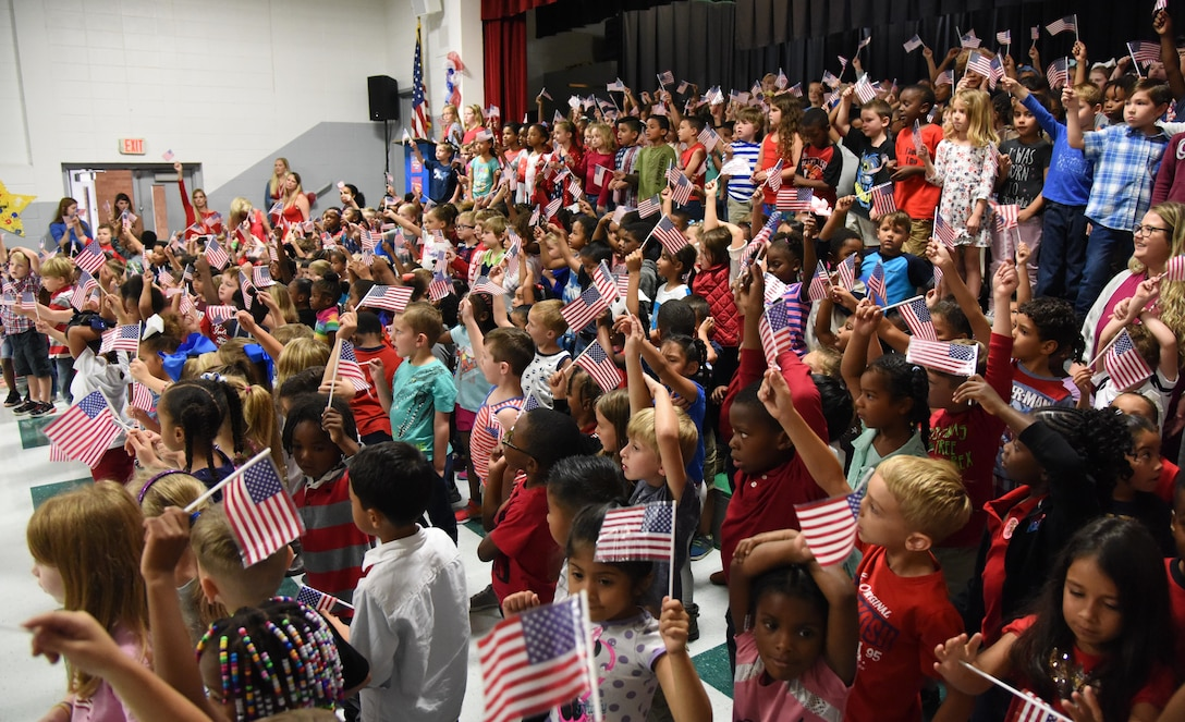 Students at Jeff Davis Elementary School sing patriotic songs during a Veterans Day celebration in Biloxi, Mississippi, Nov. 8, 2018. During the event, students also recited the Pledge of Allegiance. Keesler Air Force Base leadership, honor guardsmen and base personnel attended the event. (U.S. Air Force photo by Kemberly Groue)
