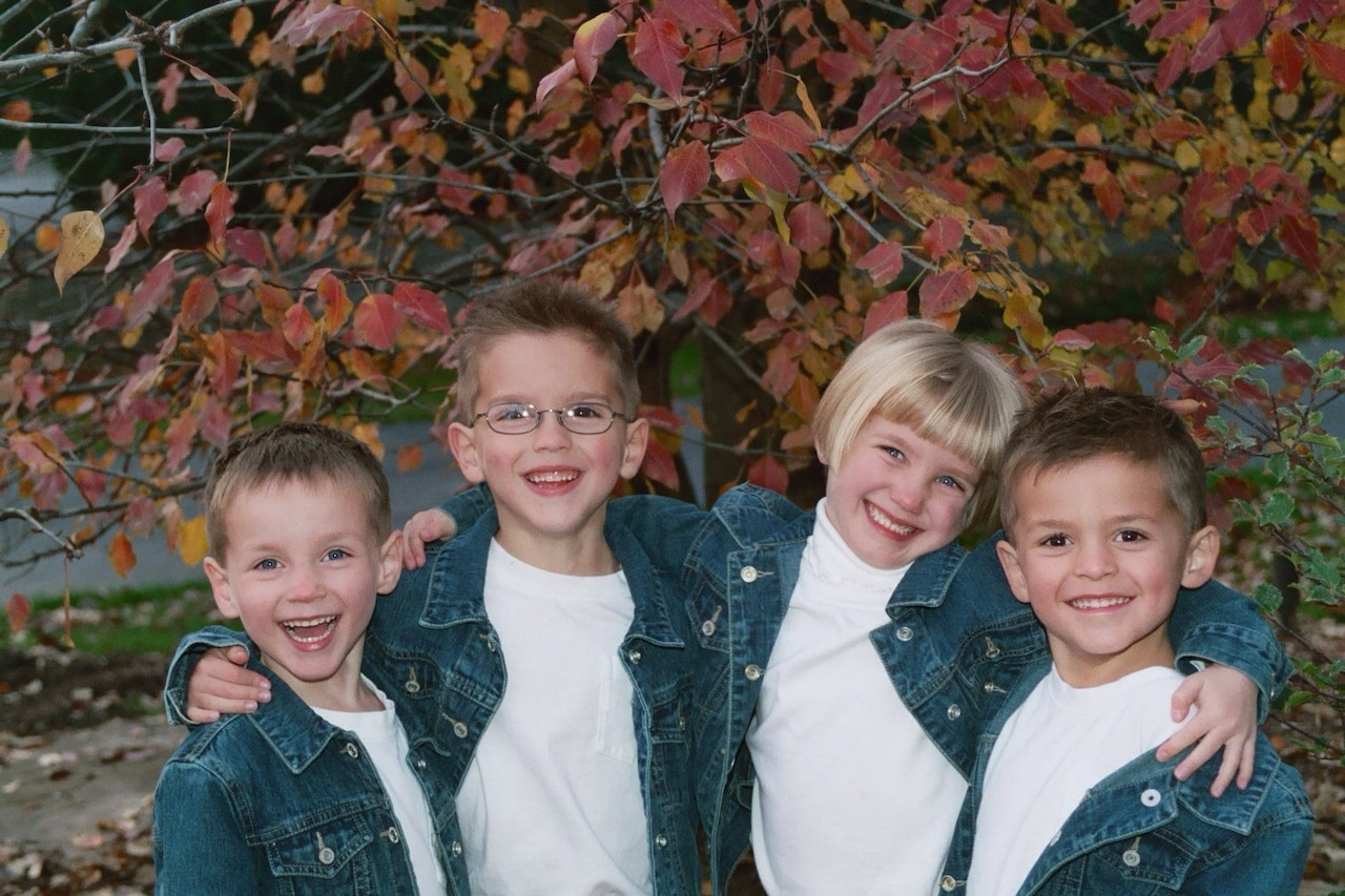 Quadruplets pose in matching outfits at a young age