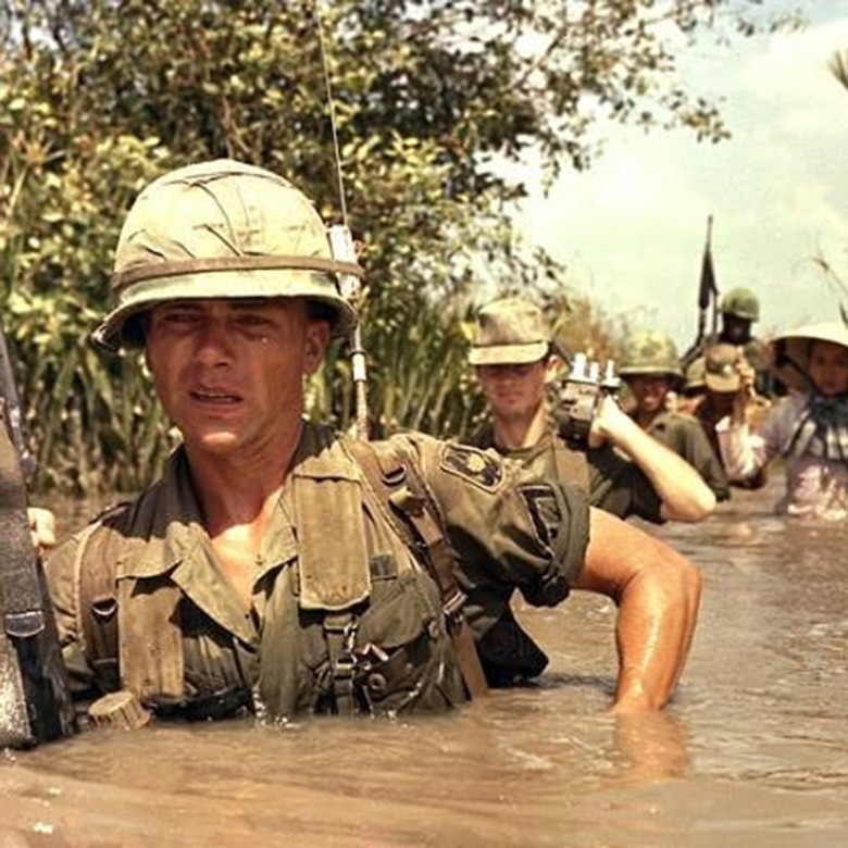 A soldier in South Vietnam takes the lead in chest-deep water.