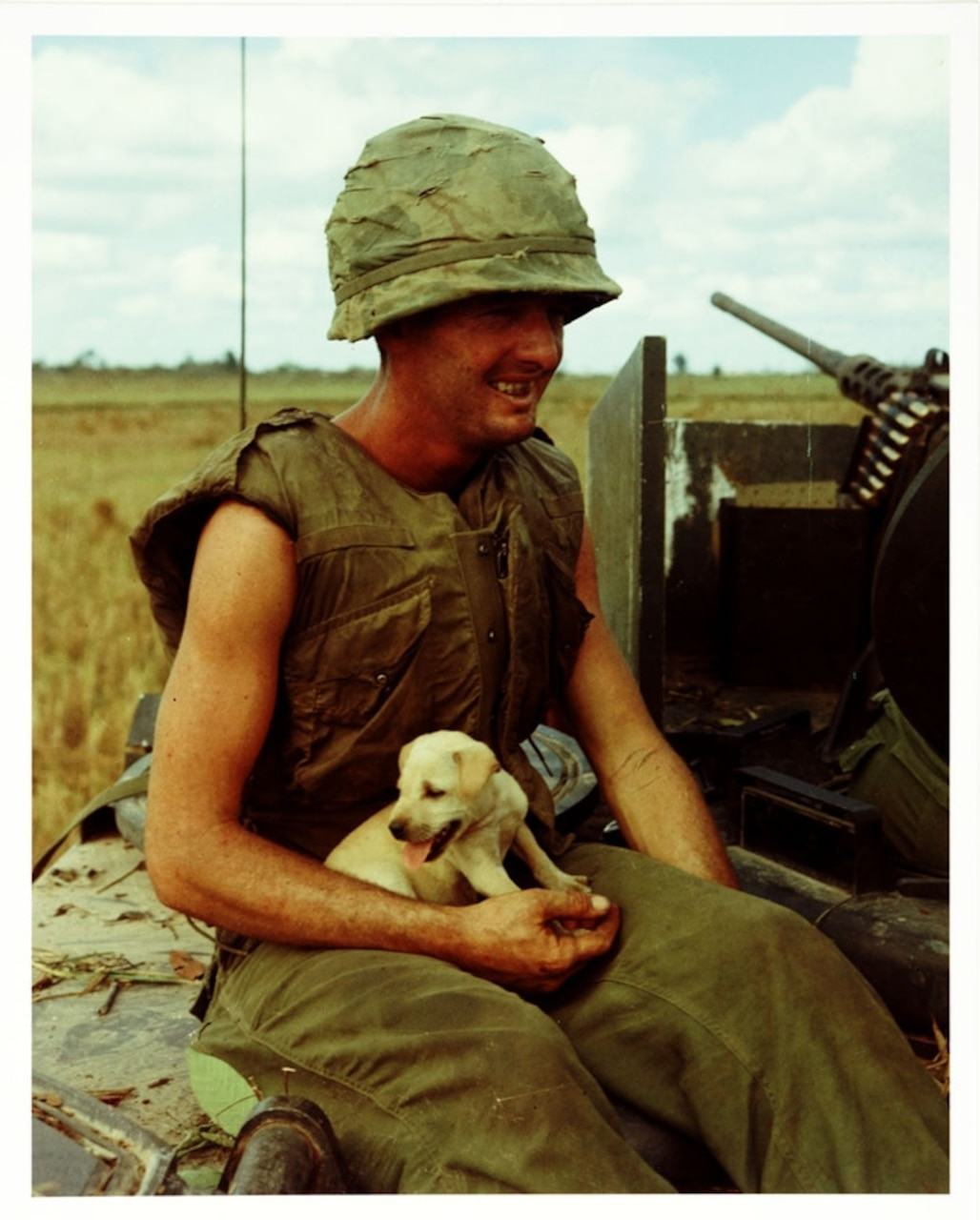 A soldier in South Vietnam sits smiling with puppy in his lap.