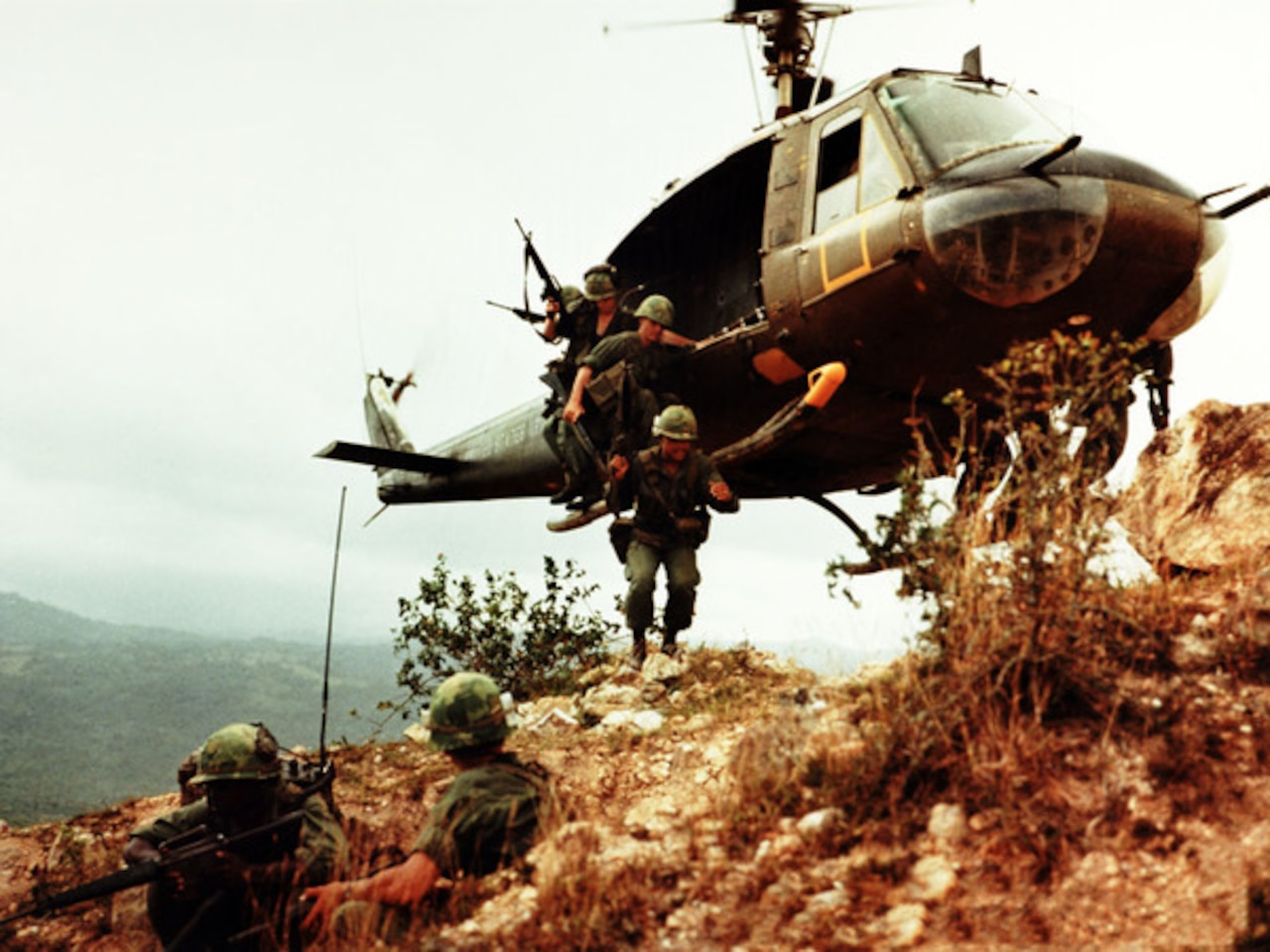 Soldiers jump out of a helicopter hovering close to the ground in South Vietnam.