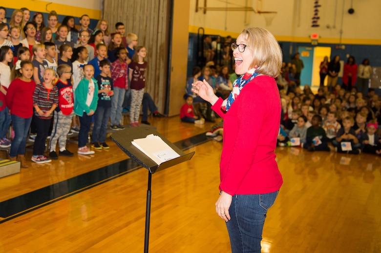 """Diane Walls, George Welch Elementary School choir director, leads the choir in the singing of """"The U.S. Air Force"""" song at a Veterans Day celebration Nov. 9, 2018, at Dover Air Force Base Middle School, Dover Air Force Base, Del. The choir performed songs in honor of each of the five military branches and the veterans in attendance. (U.S. Air Force photo by Mauricio Campino)"""