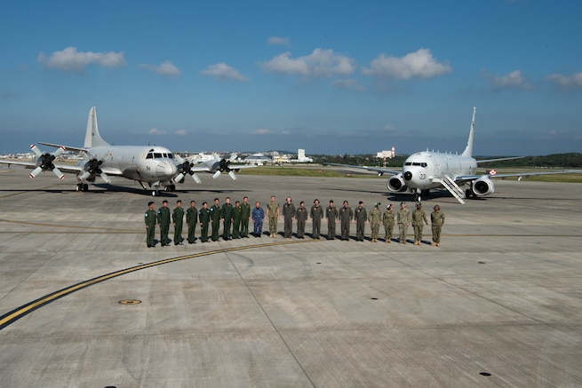 U.S. Navy Adm. Phil Davidson, commander of U.S. Indo-Pacific Command, and Joint Japan Staff Adm. Katsutoshi Kawano, Chief of Staff, pose for a photo with aircrews at Kadena Air Base Nov. 7, 2018.