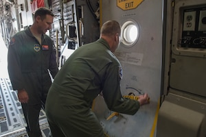 U.S. Air Force Maj. Gen. Mark Weatherington, Air Education and Training Command deputy commander, opens one of the exits on a C-17 Globemaster III, Nov. 8, 2018, at Altus Air Force Base, Okla. The 97th LRS showcased loading cargo onto a C-17, which was part of the Weatherington's tour of the bases capabilities. (U.S. Air Force photo by Senior Airman Cody Dowell)