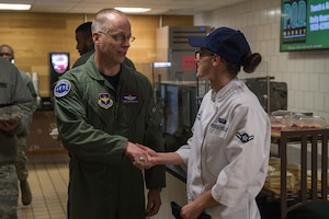 U.S. Air Force Maj. Gen. Mark Weatherington, Air Education and Training Command deputy commander, shakes the hand of Airman Katie Pease-Keller, a food services apprentice assigned to the 97th Force Support Squadron, Nov. 8, 2018, at Altus Air Force Base, Okla. Enlisted leaders gathered at Hangar 97 to have breakfast with Weatherington when he was touring the base. (U.S. Air Force photo by Senior Airman Cody Dowell)