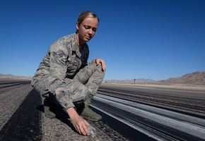 Senior Airman Sierra Rodwick, 57th Operations Support Squadron airfield management shift lead, removes foreign object and debris from a runway Oct. 15, 2018 on Nellis Air Force Base, Nevada. The professionalism and urgency demonstrated by airfield management on a daily basis are what keep Nellis a step above the rest. (U.S. Air Force photo by Airman Bailee A. Darbasie)