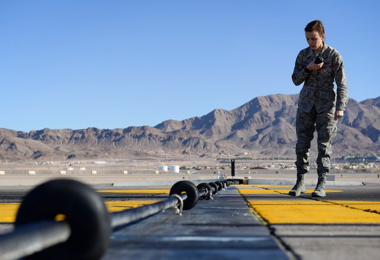 Airman 1st Class Allyson Estrada, 57th Operations Support Squadron airfield management shift lead, inspects a runway barrier Oct. 15, 2018 on Nellis Air Force Base, Nevada. Airfield management shift leads are required to complete multiple inspections per day. (U.S. Air Force photo by Airman Bailee A. Darbasie)