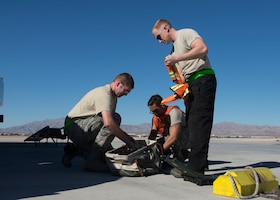 Staff Sgts. James Smith and Guy Hinton, 57th Aircraft Maintenance Squadron Raptor Aircraft Maintenance Unit dedicated crew chiefs, and Senior Airman Johnny Cruz, 57th AMXS Raptor AMU assistant DCC, prepared their gear on the flightline at Nellis Air Force Base, Nevada, Nov. 7, 2018. They performed a hot-pit refueling where an aircraft is refueled while still running to get the fighter jet back to the mission faster. (U.S. Air Force photo by Airman 1st Class Bryan T. Guthrie)