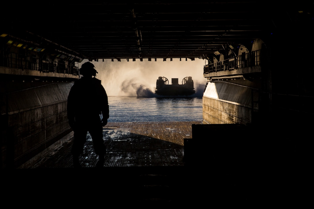 A ramp marshal prepares to guide a landing craft air cushion into USS Iwo Jima Nov. 9, 2018. The 24th Marine Expeditionary Unit back loaded vehicles and personnel Nov. 8-10 after completing exercise Trident Juncture 18. Trident Juncture is the largest NATO exercise since 2002 and allowed the 24th MEU to exercise their amphibious capabilities as a sea-based Marine Air-Ground Task Force.