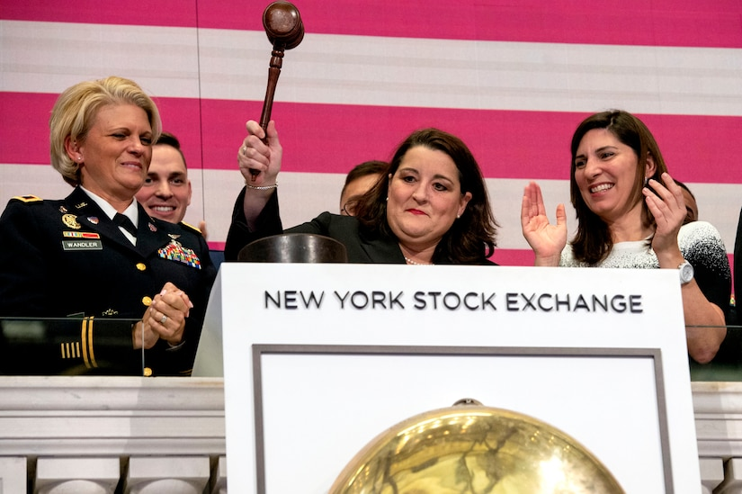 A woman stands behind a podium at the New York Stock Exchange, preparing to ring the close of business bell.