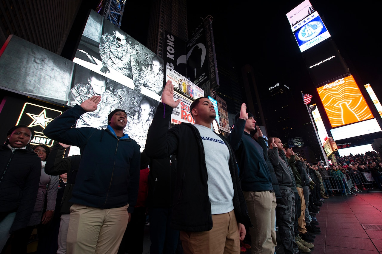 Enlistees raise their hands during a mass enlistment ceremony in Times Square in New York.