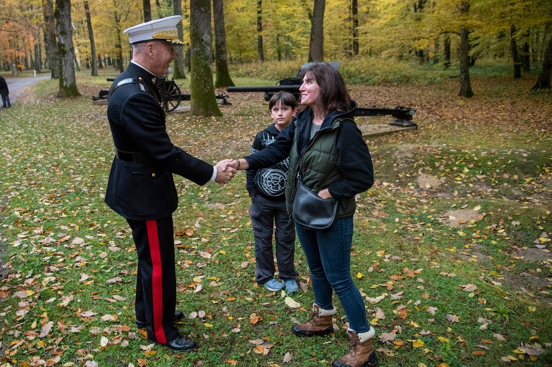 Marine Corps Gen. Joe Dunford, chairman of the Joint Chiefs of Staff, shakes the hand of a woman standing with a child.