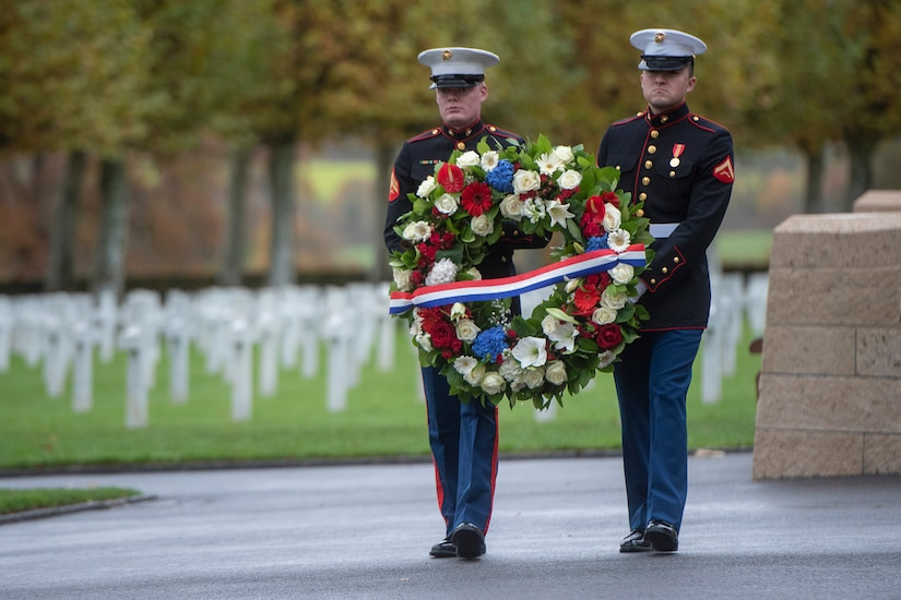 Two U.S. Marines carry a wreath at a cemetery.