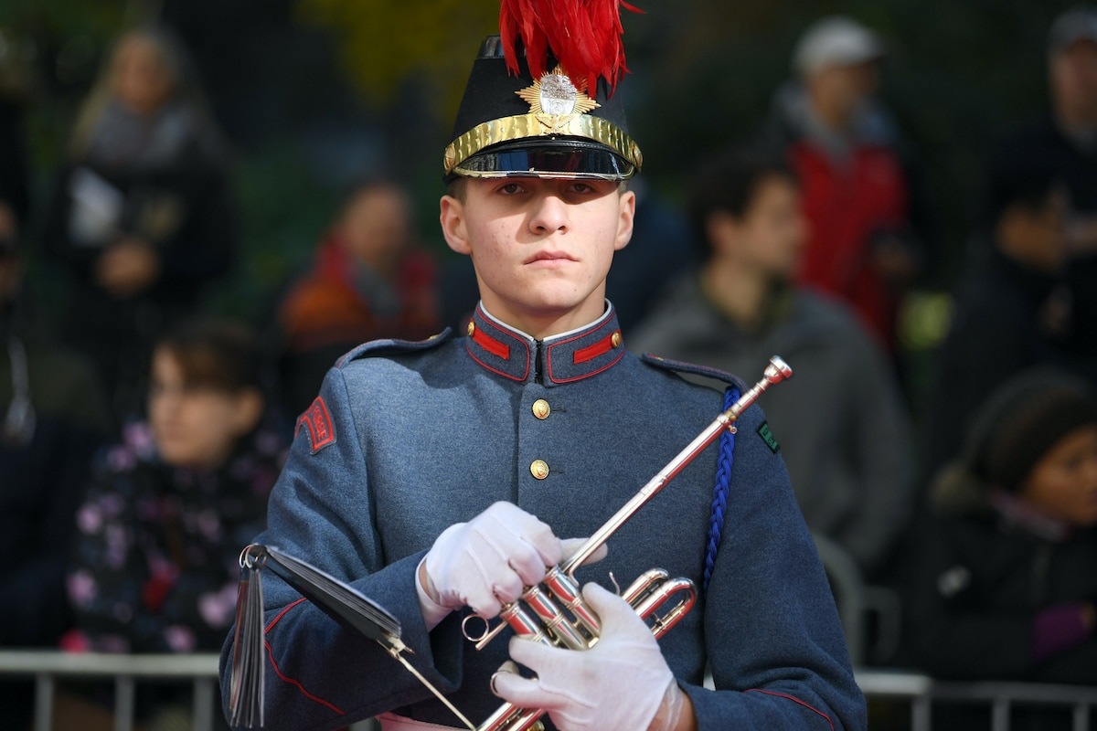 A trumpeter in uniform holds a trumpet.