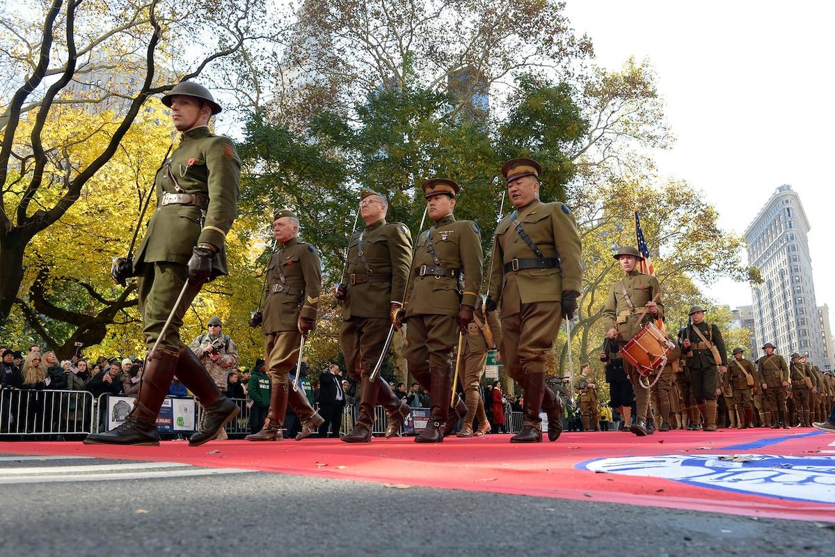 WWI reenactors in uniform march in a parade
