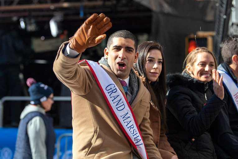 A man wearing a grand marshal sash waves to parade watchers from a car.