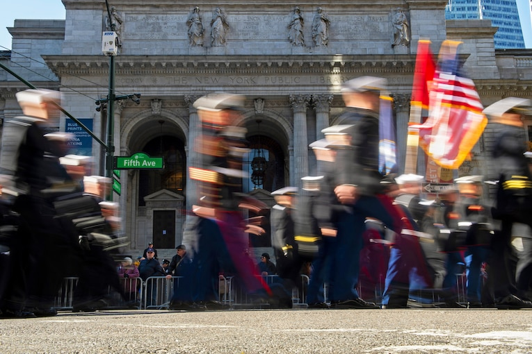 Spectators watch as a blur of Marines and sailors march past the New York Public Library.