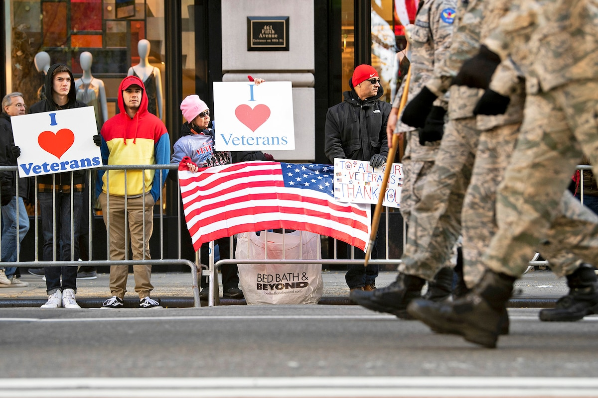 Spectators hold signs supporting veterans along the 2018 Veterans Day Parade route.